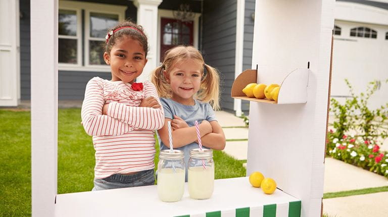 Two young children selling lemonade